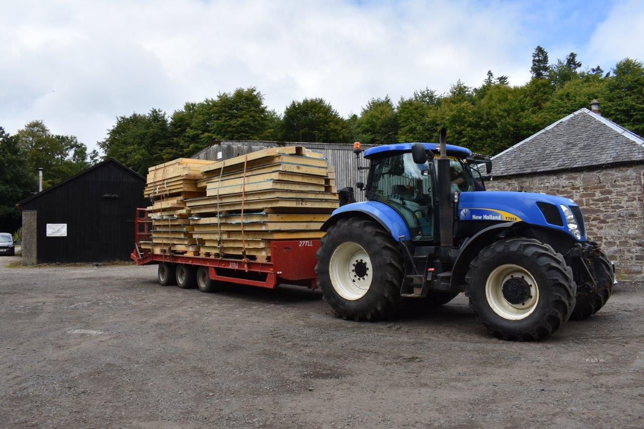 Tractor and low loader carrying wood